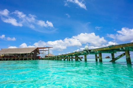 Wooden path to the bungalow above water on tropical island