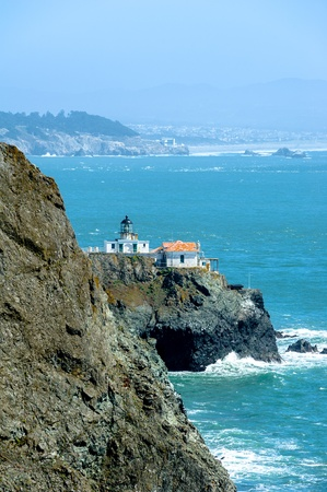 Rocky coastline and lighthouse in California, USA photo