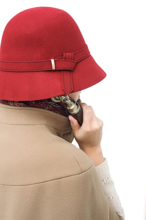 Old-fashioned woman in red hat holding telephone receiver and talking or listening photo