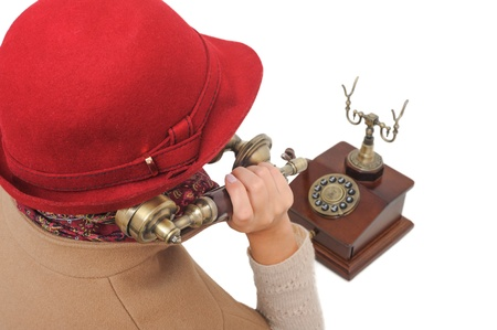 Old-fashioned woman in red hat is talking old-fashioned phone on white isolated background photo