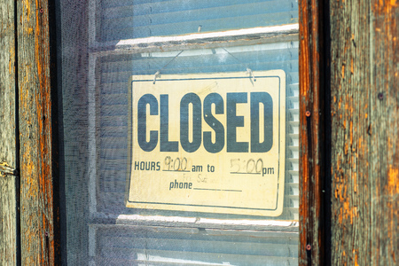 shop sign: Old wooden door with hanging Closed sign