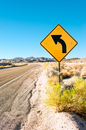 Road in the desert and turn sign photo