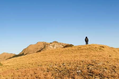 A man stand on the mountain with golden sunshine. photo