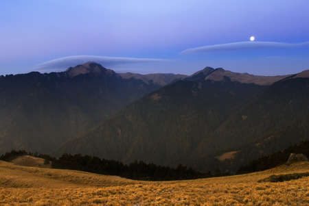 Moon rised and shining over the high mountain. photo