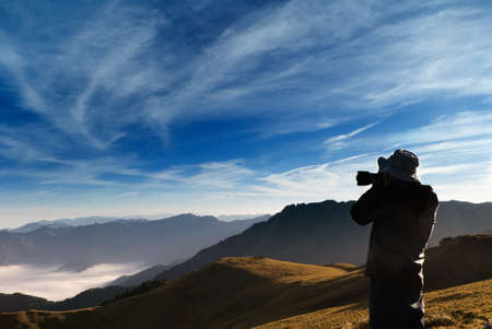 capturing: A cameraman standed and shot whith clouds in the outdoor.