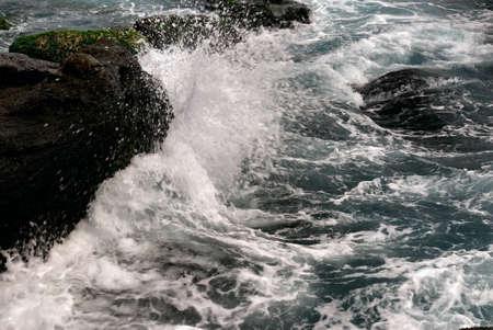 paliza: Es potente olas golpeando la roca.