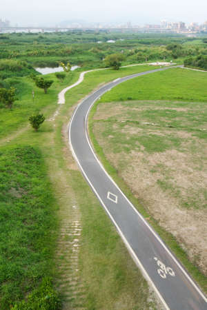 It is a road for bicycle on the grassland. photo