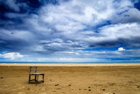 It is a lonely one chair on the beach.