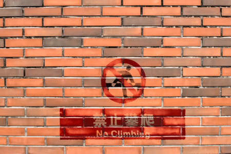 It is a red stone wall with no climbing sign in Chinese. Stock Photo - 5352487