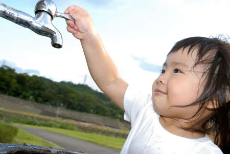 She is a happy baby washing her hand and turn off faucet in the outdoor. Stock Photo - 5496031