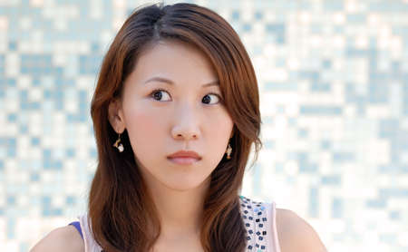 Here is a beautiful Asian lady in front of mosaic and watching. Stock Photo - 5496034