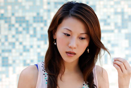 Here is a beautiful Asian lady in front of mosaic and watching. Stock Photo - 5496028