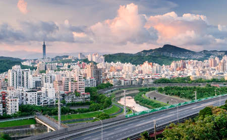 It is a cityscape photo of apartments and highway. photo