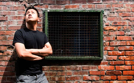 There is a lonely Asian man against old window. Stock Photo - 5528953
