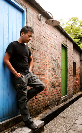 There is an Asian man stand against a old door and lonely. photo