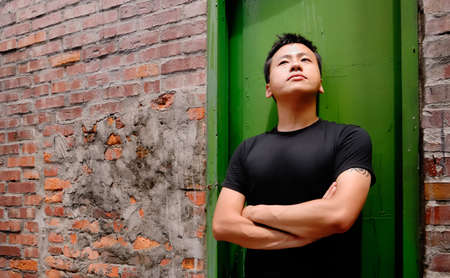 There is an Asian man stand against a old door and lonely. Stock Photo - 5528955