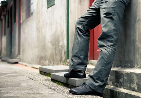 homme triste: Il est des jambes de l'homme debout contre le mur. Banque d'images