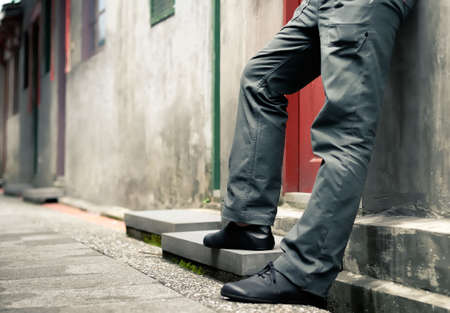 gente triste: Se trata de las piernas del hombre de pie contra la pared. Foto de archivo