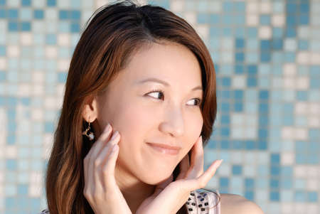 Here is a beautiful Asian lady in front of mosaic and watching. Stock Photo - 5569385