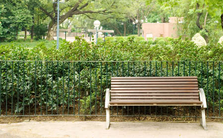 It is a brown bench with nobody in the park. photo