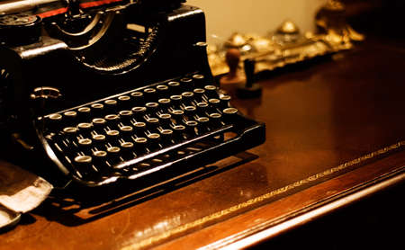 It is an old typewriter for bank on the desk. photo
