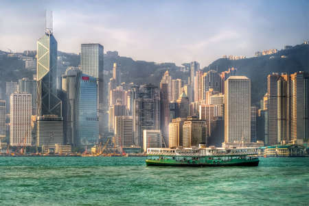 Famous ferry on Victoria harbor in Hong Kong with tall buildings. photo