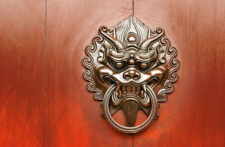 赤い壁の青銅色のライオンの中国の装飾。