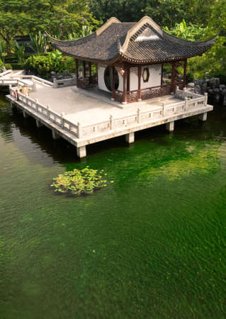Beautiful Chinese wooden building near the green pond. Stock Photo - 5844792