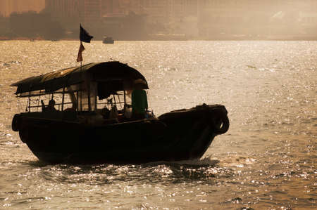 Silhouette of fishing boat with dramatic sunset light in Hong Kong. Stock Photo - 5845000