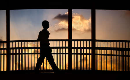Silhouette of businessman after work walking on the bridge with sunset clouds and light. photo