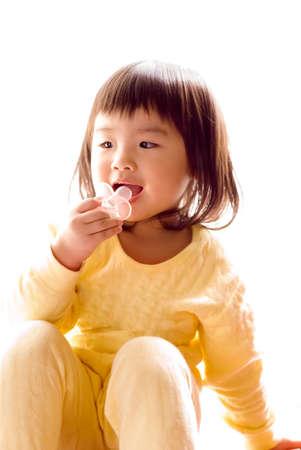 pacifier: Bebé de Asia Lovely sentarse y succionar el chupete en el fondo blanco. Foto de archivo