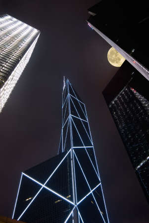 Night scenes of modern skyscraper with moon in Hong Kong. photo