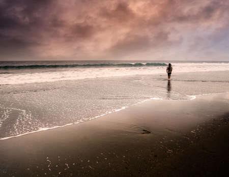 One man walking along the waters edge on a fantasy beach. photo