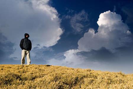walking alone: Un hombre de pie sobre la colina y ver en alg�n lugar lejos.