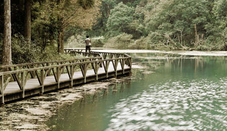 Landscape of lake with single man and forest. Stock Photo - 6053375