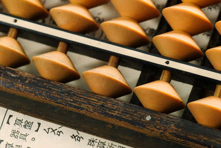 multiplying: Traditional abacus lay on a paper write in Chinese words.