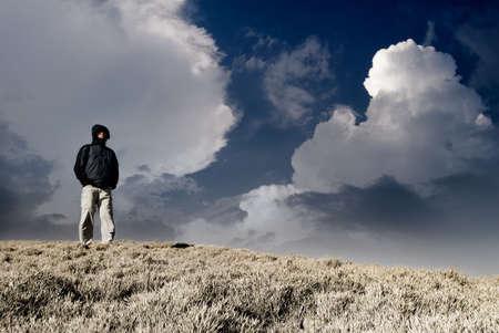 Stand uomo solitario e orologio sulla collina con cielo drammatico.
