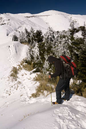 Mountain climber on snow peak with backpack and trekking pole. photo