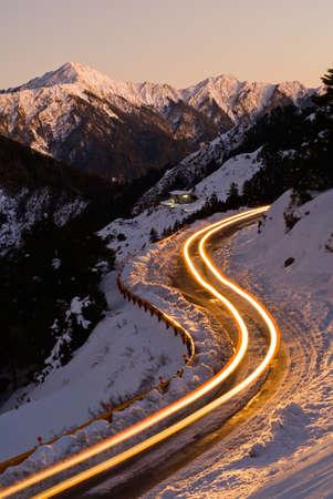 Coche de luz en la noche en la carretera de hielo en invierno montaña de nieve.