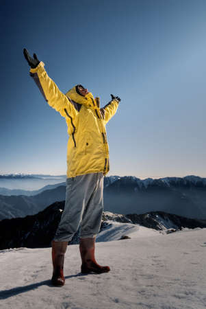 Man with open arms against blue sky on white snow hill. photo