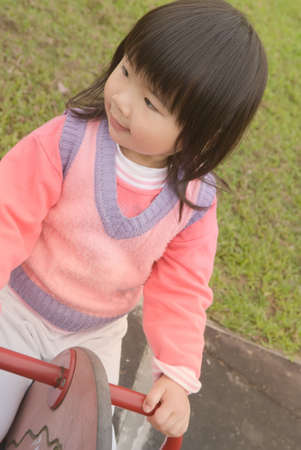 Asian baby with black hair and yellow skin in pink coat play in outdoor of park. Stock Photo - 6351610