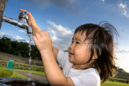 faucets: Cute Asian children wash hands in park.