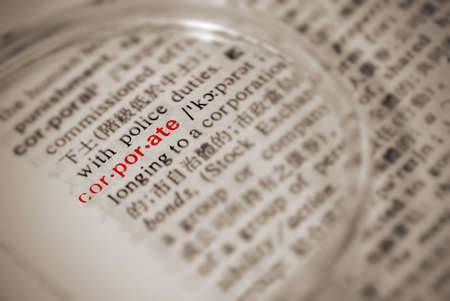 Corporate definition in dictionary with magnifier in yellow color. photo
