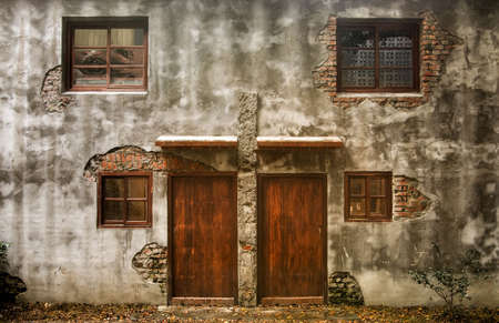 Ruins of old wall and brown door and dark windows of discarded building. Stock Photo - 6480608