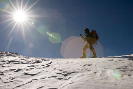 Man of mountain climber walk in snow winter day with sun light flare. photo