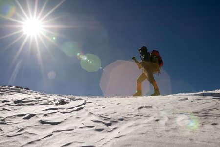 mountain climber: Uomo di montagna scalatore passeggiata nella neve invernale giorno con riflesso di luce di sole.