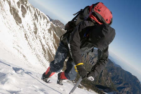 Mountain climber use ice axe to walk on snow ice slop in winter. photo