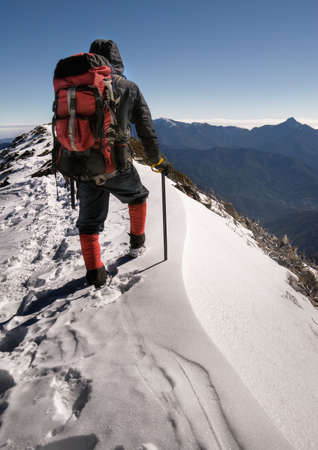 ice climbing: Single man of climber walk alone on top of snow ice winter mountain. Stock Photo