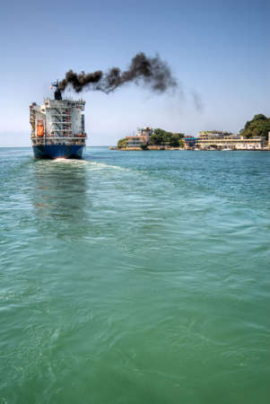 polluting: Freighter navigate the port with black smoke of sea in Kaohsiung, Taiwan.