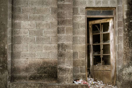 Old building of discarded with stone wall and broken door and window. photo